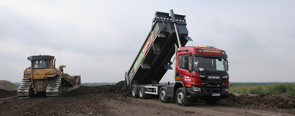 Tipper truck delivering soil to a landfill restoration site.